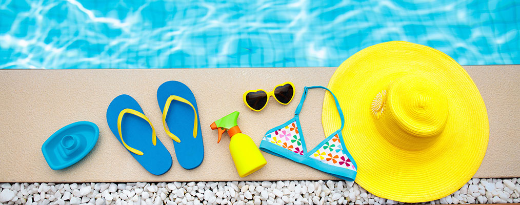 Swimming pool accessories flat lay. Top view of beach items on pool deck. Flip flops bikini and hat sun glasses. Water toys. Summer vacation in tropical resort. Copy space. Colorful beach wear.