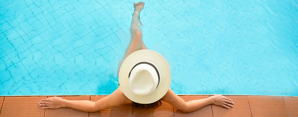 Asia woman lifestyle relaxing near luxury swimming pool sunbath summer day at the beach resort in the hotel. Concept Summer