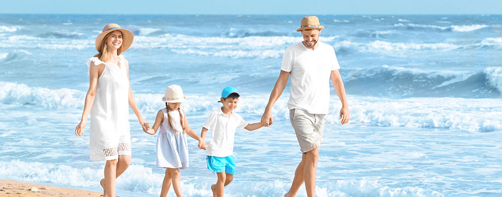 Happy family on sea beach at resort