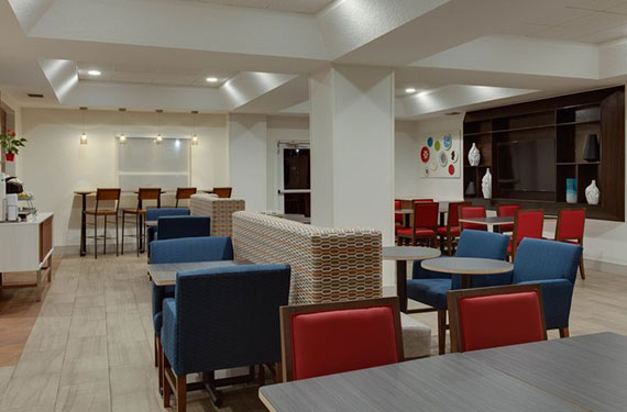 seating area and tables in lobby of Holiday Inn Express Orlando Airport hotel