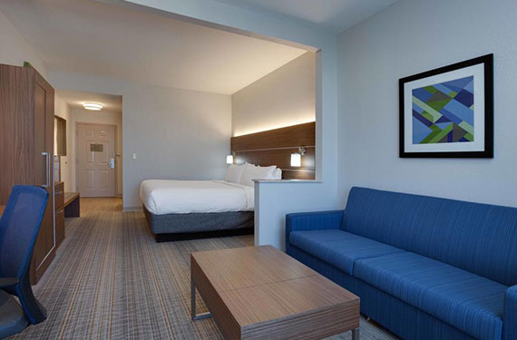 king bed, desk, sofa, and coffee table in a Holiday Inn Express Orlando Airport hotel room'