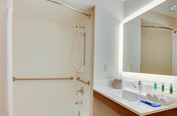 shower, sink, counter, and mirror in a Holiday Inn Express Orlando Airport hotel room bathroom'