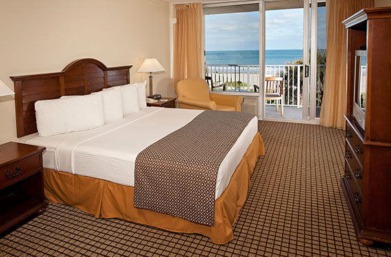 king bed, dresser, TV, and night stands in an International Palms Cocoa Beach hotel room'