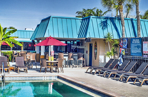 outdoor pool, lounge chairs, umbrella tables, and chairs at International Palms Cocoa Beach'