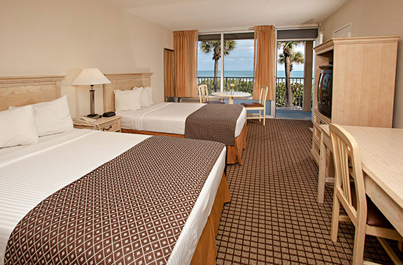 2 double beds, dresser, TV, night stand, lamp, desk, and chair in an International Palms Cocoa Beach hotel room