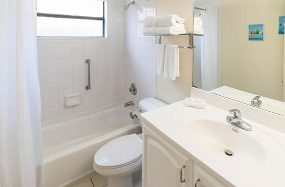 tub with shower, toilet, counter, sink, and mirror in an International Palms Cocoa Beach hotel room bathroom'