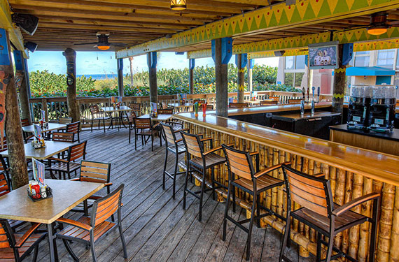 outdoor bar, bar stools, tables, and chairs for dining at  International Palms Cocoa Beach hotel'