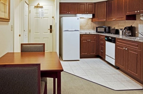 dining table and chairs, and full kitchen in a Staybridge Suites Orlando Airport hotel room'