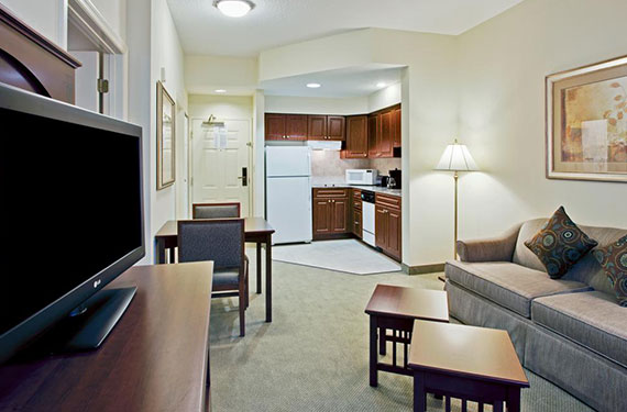 view of TV, dining table and chairs, full kitchen, sleeper sofa, and coffee tables in a Staybridge Suites Orlando Airport hotel room