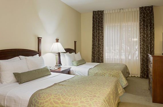 2 queen beds, night stand, lamp, and dresser in a Staybridge Suites Orlando Airport hotel room