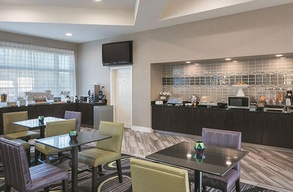 dining tables and chairs next to La Quinta Inn Airport North hotel's breakfast buffet 