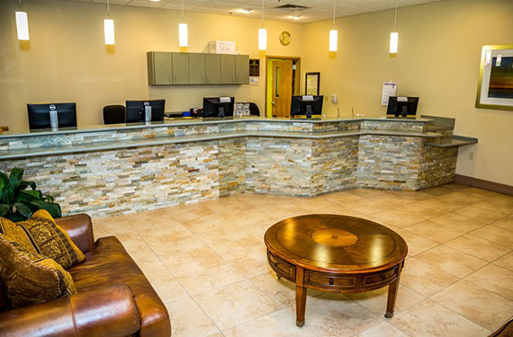 front desk, coffee table, and couch in Ocean Landings Cocoa Beach hotel lobby'