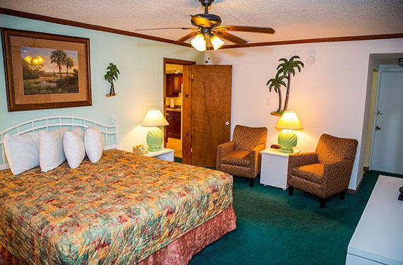 king bed, side tables, and chairs in an Ocean Landings Cocoa Beach hotel room'