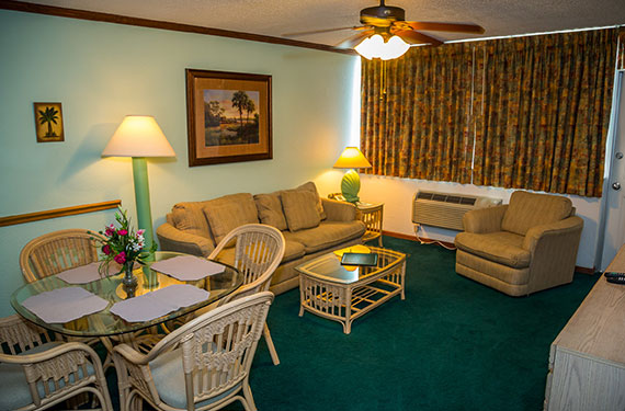 dining table and chairs, couches, coffee table, and chair in a Ocean Landings Cocoa Beach hotel room'