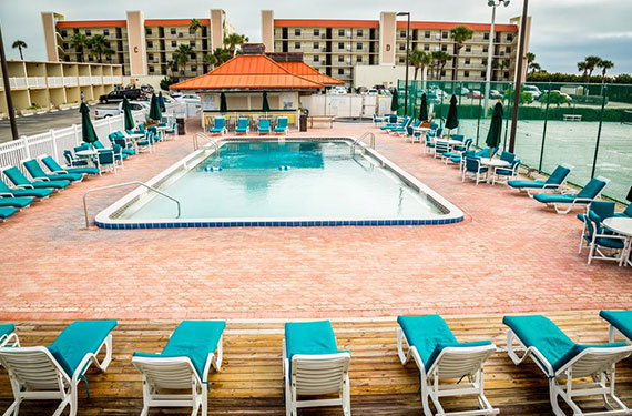 outdoor pool and lounge chairs at Ocean Landings Cocoa Beach hotel