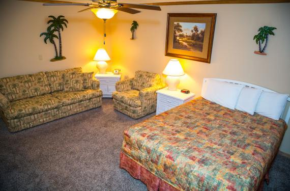 queen bed, sleeper sofa, chair, side tables, and lamps in an Ocean Landings Cocoa Beach hotel room'