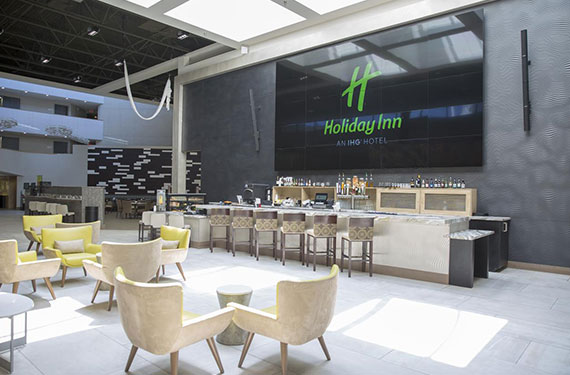 bar, bar stools, and seating area at Holiday Inn Orlando Airport'