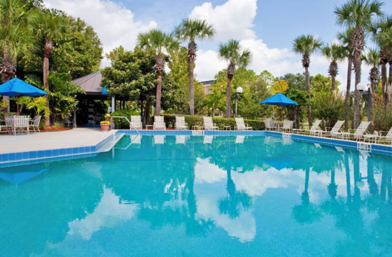 outdoor pool, lounge chairs, and umbrellas at Holiday Inn Orlando Airport hotel'