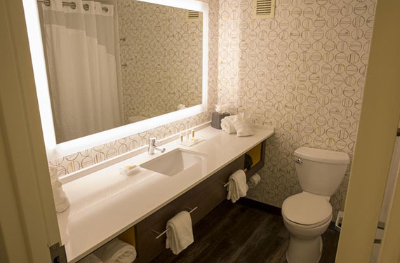 toilet, sink, counter, and mirror in a Holiday Inn Orlando Airport hotel room bathroom'