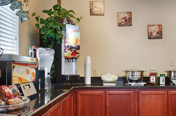 complimentary breakfast buffet counter at Best Western Titusville featuring hot items, baked goods, and variety of beverages