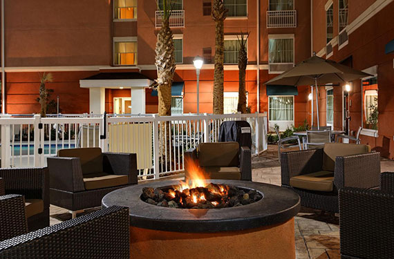 chairs around fire pit next to outdoor pool at Homewood Suites Orlando Airport Gateway Village hotel