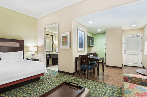 view of king bed, sleeper sofa, bathroom, table and chairs, in a Homewood Suites Orlando Airport Gateway Village hotel room
