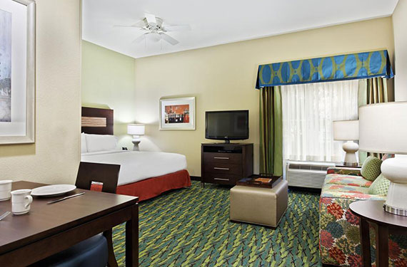 view of king bed, dresser, TV sleeper sofa, lamps, table, and chair in a Homewood Suites Orlando Airport Gateway Village hotel room
