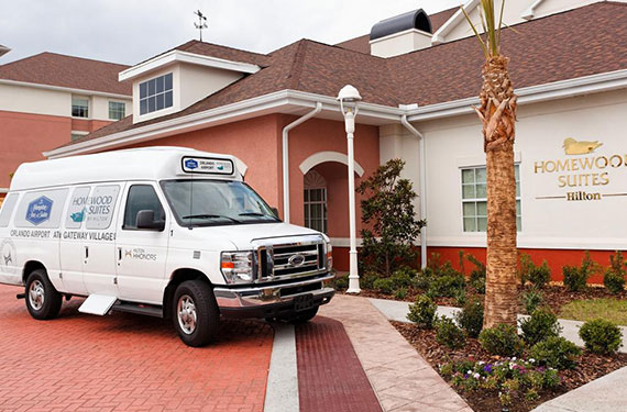 exterior view of Homewood Suites Orlando Airport Gateway Village hotel and hotel shuttle in front of lobby