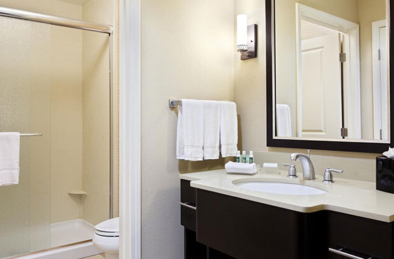 shower, counter, sink, and mirror in a Homewood Suites Orlando Airport Gateway Village hotel room bathroom