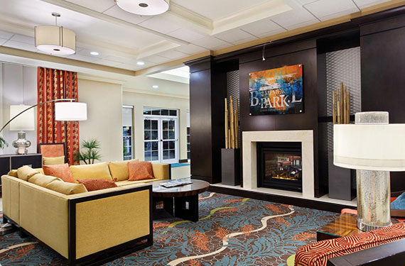 couch and fireplace in Homewood Suites Orlando Airport Gateway Village hotel lobby