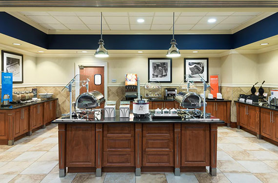 view of complimentary buffet breakfast serving area at Hampton Inn Orlando Airport Gateway Village featuring items like eggs, bacon, waffles, cereal, fresh juices, coffee, and variety of baked goods