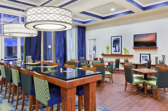 tables and chairs for dining in Hampton Inn Orlando Airport Gateway Village hotel