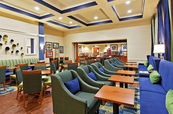 dining tables, chairs, and booth seating at Hampton Inn Orlando Airport Gateway Village hotel
