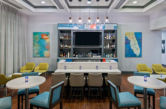bar and bar stools, and tables and chairs at Hampton Inn Orlando Airport Gateway Village hotel