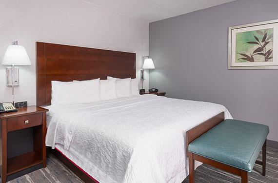 king bed, night stands, and lamps in a Hampton Inn Orlando Airport Gateway Village hotel