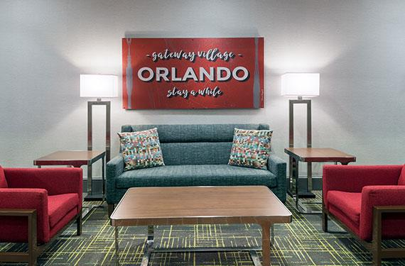 couch, coffee table, chairs, lamps, in Hampton Inn Orlando Airport Gateway Village hotel lobby seating area