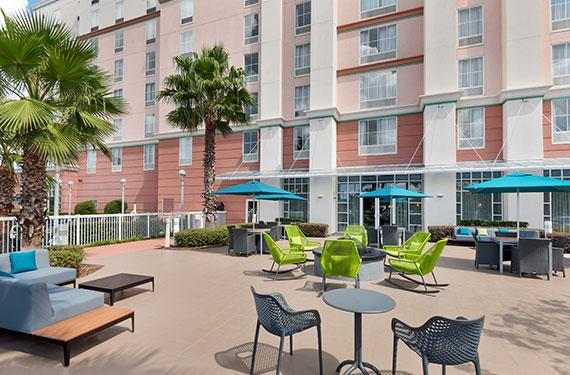 outdoor fire pit, umbrellas, and seating outside of Hampton Inn Orlando Airport Gateway Village hotel