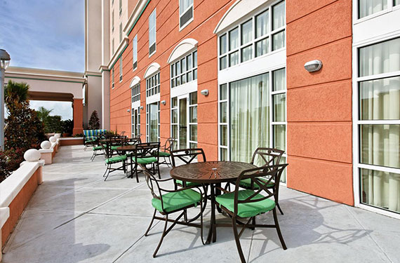 tables and chairs outside of Hampton Inn Orlando Airport Gateway Village hotel