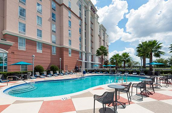 view of outdoor pool and chairs at Hampton Inn  Orlando Airport Gateway Village hotel