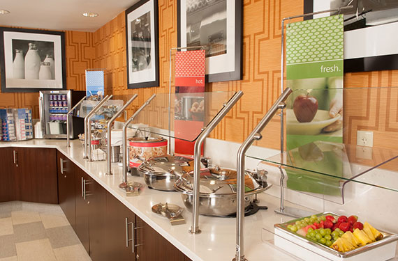 complimentary hot buffet breakfast serving counter at Hampton Inn Orlando Airport hotel'