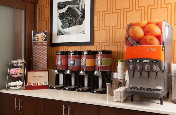 hot and cold beverage station at Hampton Inn Orlando Airport featuring a variety of juices, coffee, and tea '
