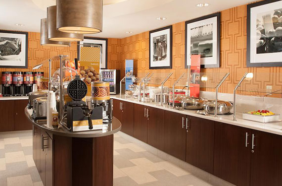 view of complimentary hot buffet breakfast serving counter and waffle station at Hampton Inn Orlando Airport hotel'