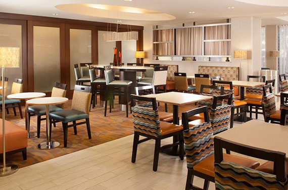 tables and chairs in breakfast dining area at Hampton Inn Orlando Airport hotel'