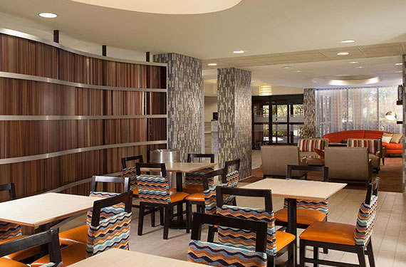 tables and chairs in dining area at Hampton Inn Orlando Airport hotel'