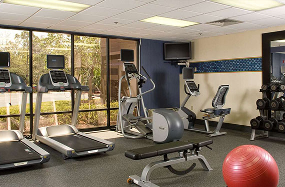 treadmills, weights, and other gym equipment at Hampton Inn Orlando Airport hotel fitness center '