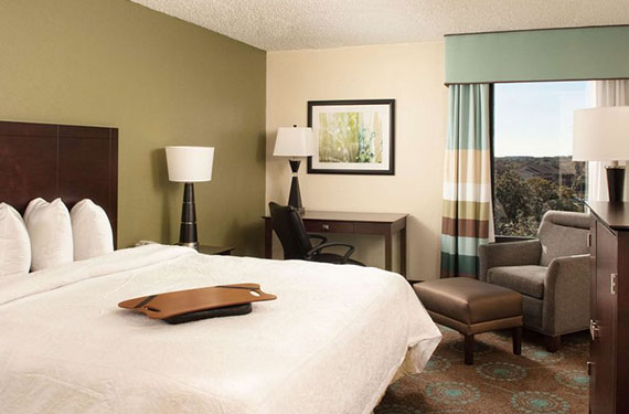 king bed, side table, lamps, dresser, desk, desk chair, and armchair with foot rest in a Hampton Inn Orlando Airport hotel room'