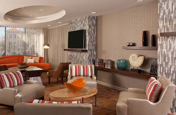 couches, chairs, tables, and TV at Hampton Inn Orlando Airport hotel common area