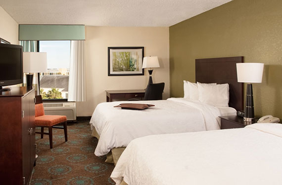 2 queen beds, dresser, TV, nightstand, lamps, desk, and chairs in a Hampton Inn Orlando Airport hotel room'
