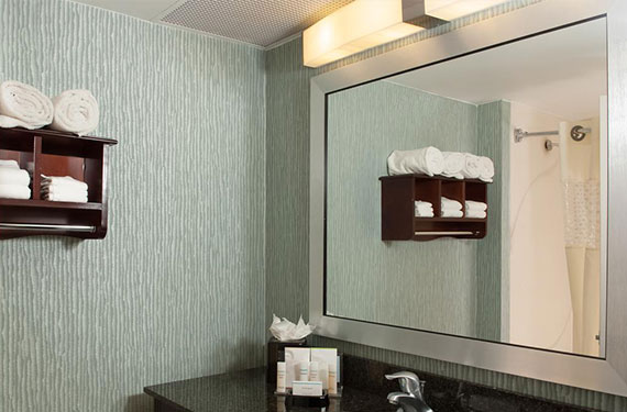 bathroom counter, mirror, and shower in a Hampton Inn Orlando Airport hotel room'