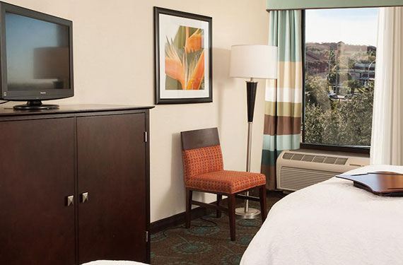 dresser, TV, end of bed, chair, and lamp in a Hampton Inn Orlando Airport hotel room
